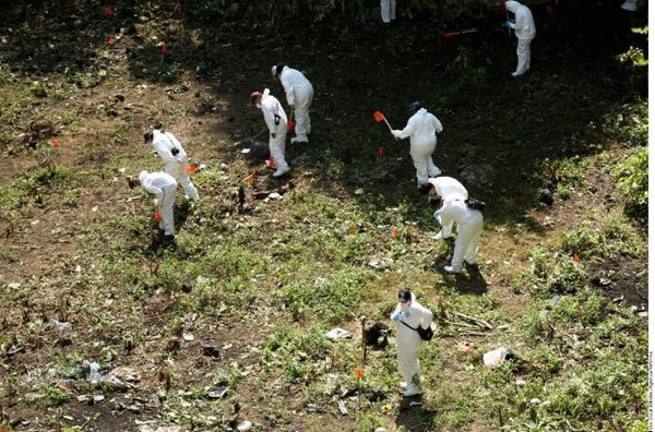 Investigators at the Cocula dump, where the students' bodies were believed to have been burned.