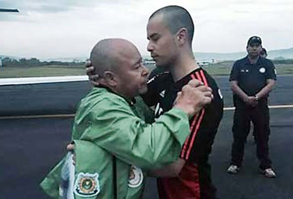 Montes de Oca is greeted by his father after his release from jail.