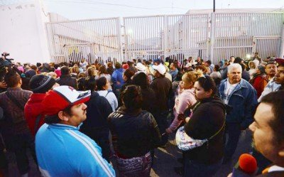 Family members gather outside the prison this morning.