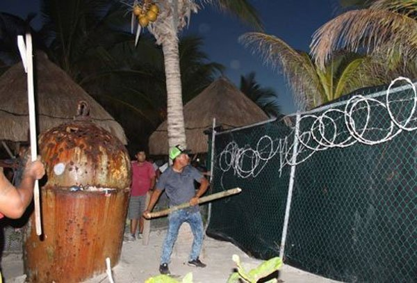 A protester attacks the fence Sunday in Akumal.