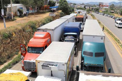Trucks are halted by teachers on a Oaxaca highway.
