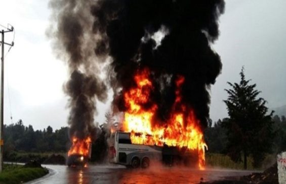 A bus and another vehicle burning yesterday in Michoacán.