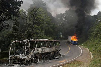 A burned-out bus and a burning truck yesterday in Michoacán.