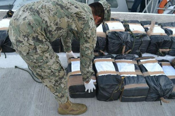 A member of the armed forces stacks packages of seized drugs