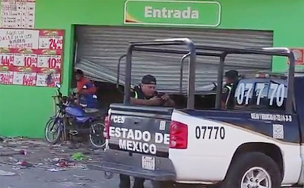 A State of México police officer checks his messages while a looter exits a Bodega Aurrera.