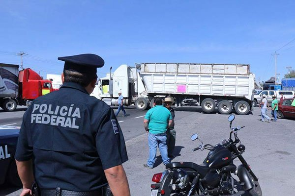 A police officer watches as a truck blocks a highway in Tlaxcala.