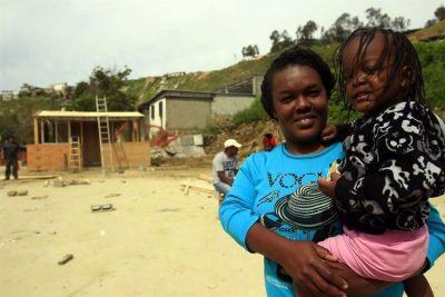A Haitian woman and her child at the site of the new housing development.