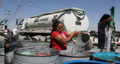 A tanker fills water storage drums in Mexico City.