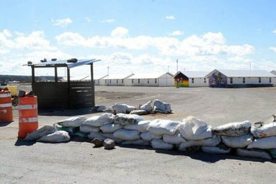 Sandbags and empty barracks at abandoned military base.