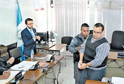 A handcuffed Duarte is led into a Guatemala courtroom yesterday.