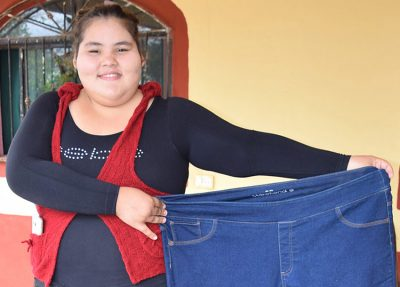 Dayana cheerfully shows off the pants that no longer fit.