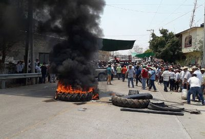 Burning tires block a road in Totolapan.