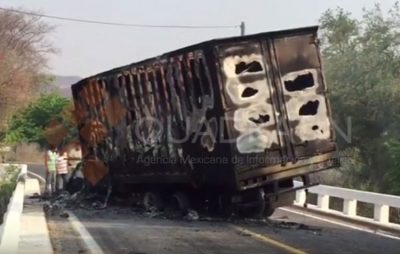 A burned-out truck blocks a road in Tierra Caliente.