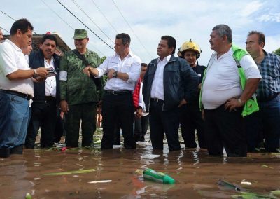Governor Murat, center, wades through floodwaters with local officials in Juchitán.