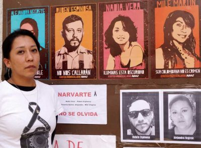 Alma Espinoza, sister of a victim, with a memorial to the dead.