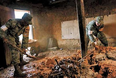 Soldiers clear mud from a house in the mountains of Oaxaca