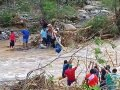 Residents of San Miguel Tenango in the isthmus region use a rope to cross a river.