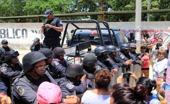 Security forces stand guard as relatives wait for information outside the Acapulco prison.