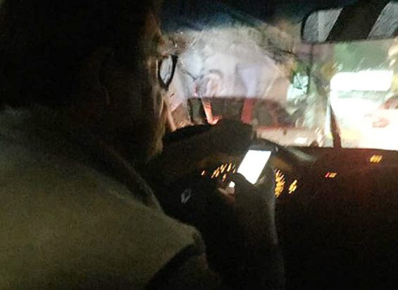 The Uber driver, cell phone in hand.