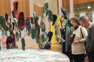 Visitors view shoes that form traveling exhibition.