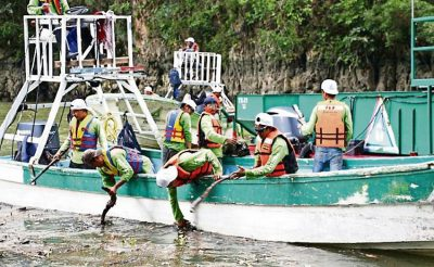 Workers remove trash from the Grijalva river.