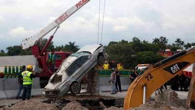 Victims' car is hoisted from the sinkhole.