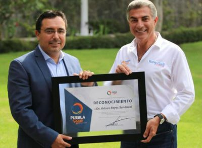 Reyes-Sandoval, left, accepts award from the Puebla governor.