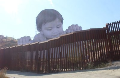 Kikito peers over the border fence.