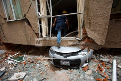 Rodrigo Díaz steps over a crushed car into what used to be a second-floor apartment at 517 Tokio in Mexico City