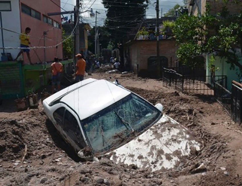 A car is left half-buried in mud following the passage of Pauline.
