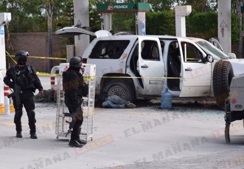 Security forces stand by after a gun fight at a Pemex station.