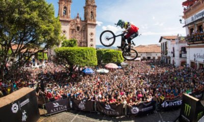 Huge crowd watches a rider in mid-jump at Downhill Taxco