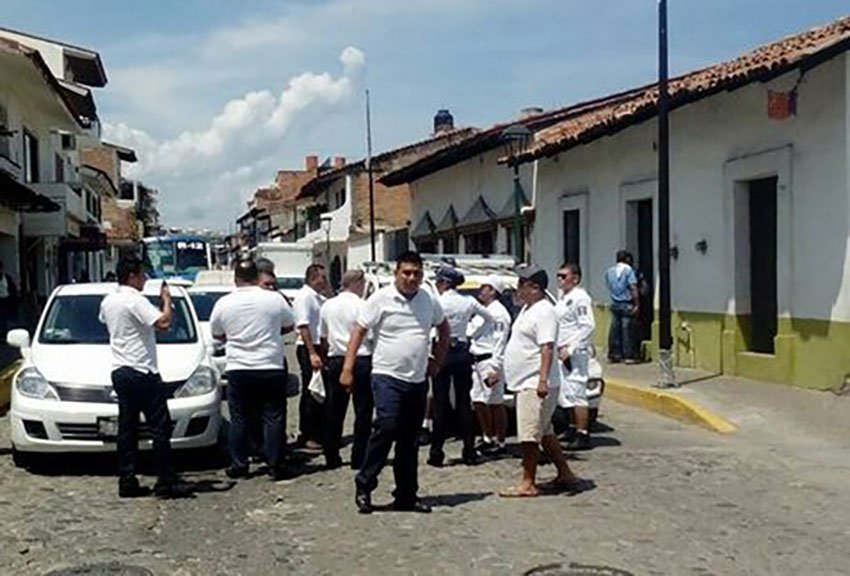 Taxi drivers surround an Uber car in Puerto Vallarta in June.
