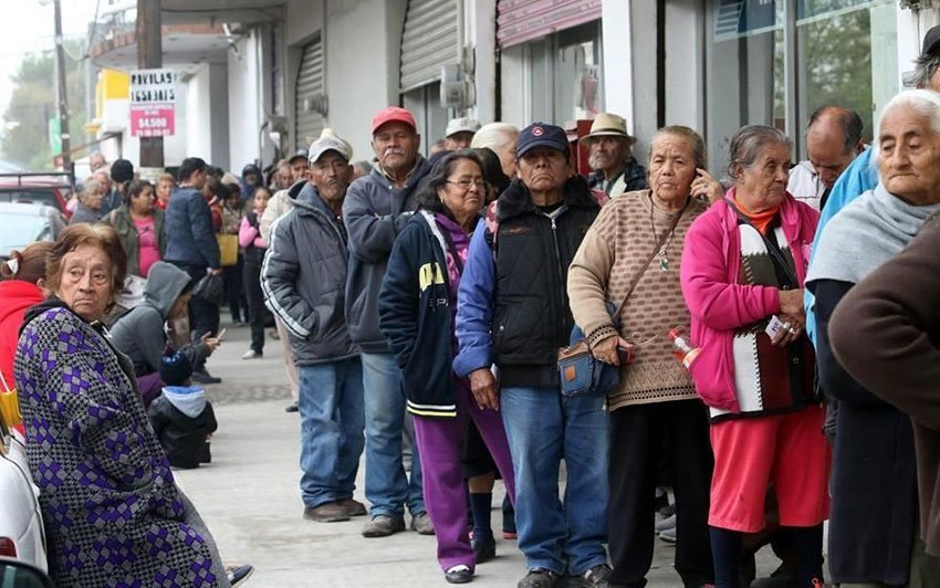 Seniors wait in line for their support payments in Monterrey.