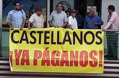 Media representatives and a banner directed at the mayor.