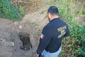 A police officer examines a hidden grave in Nayarit.