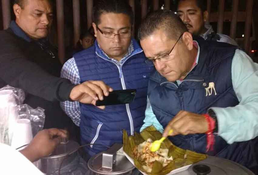A government official picks through a tamal looking for dog bones.