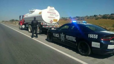 Police check a tanker truck.