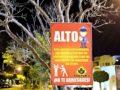 A sign warns of neighborhood vigilance.