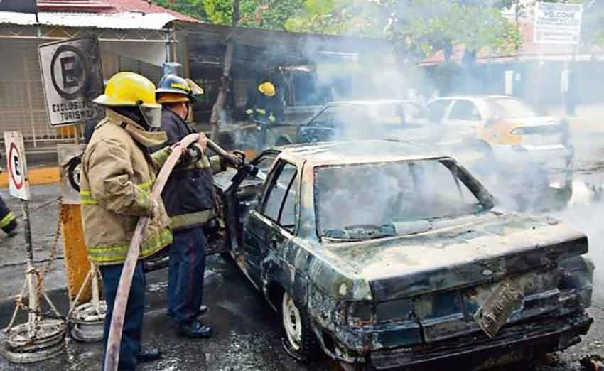 Firefighters attend to a car that was set on fire in Acapulco.