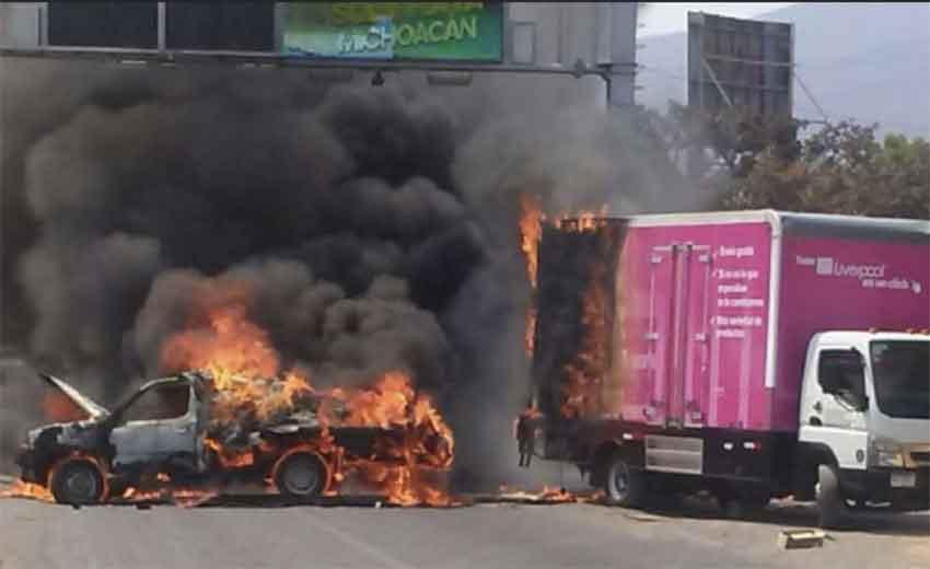 Vehicles burn after gangsters retaliate.