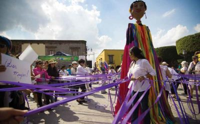 Women of Ser Mujer celebrate with a mojiganga, or giant puppet, in the Jardín.