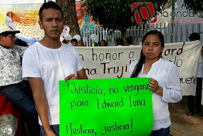 Edward's parents with a sign that reads, 'Justice, not revenge, for Edward Luna.'
