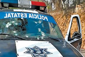 Patrol vehicle riddled with bullet holes.