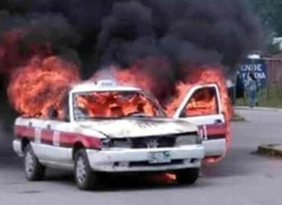 A taxi burns in Altamirano, Chiapas, yesterday.