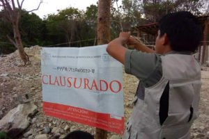 A Profepa official posts a closed sign on one of the projects in Tulum.