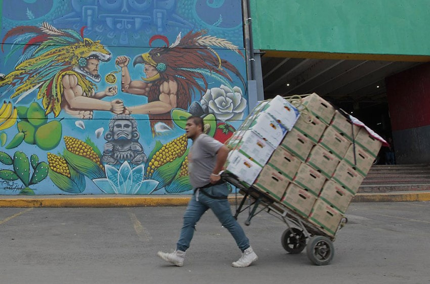 A man pulls a produce cart past one of the existing murals at the Mexico City market.