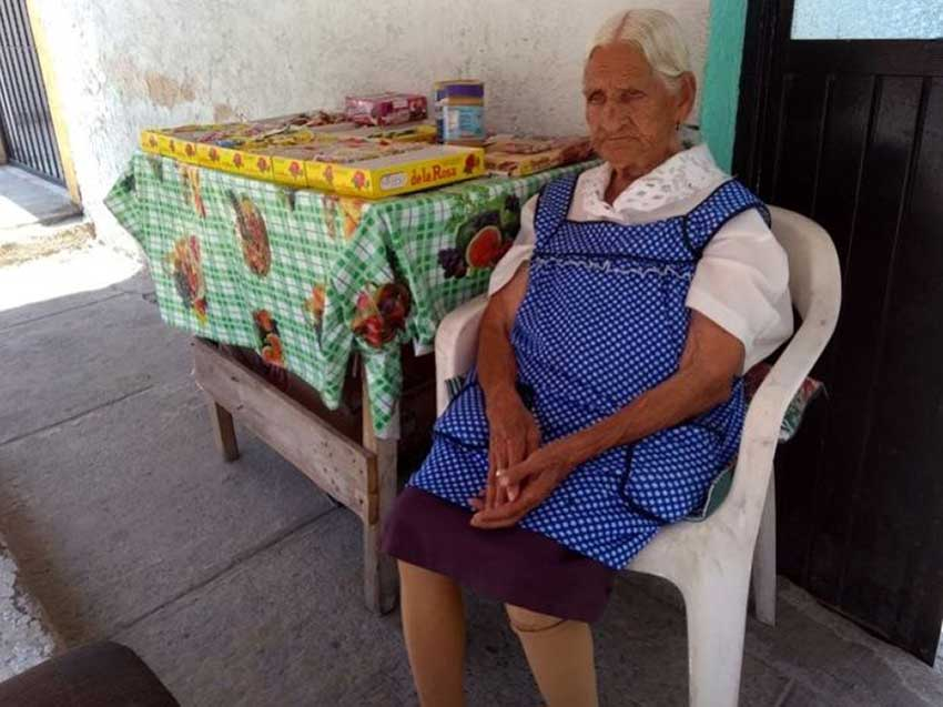 Jalisco's oldest woman sells candy on the sidewalk outside her home.