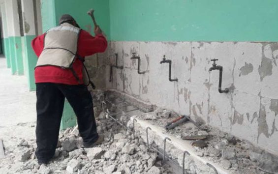 A worker carries out repairs at a school damaged by earthquakes.