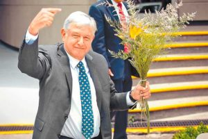 López Obrador greets supporters, who presented him with a bouquet of flowers, after yesterday's ceremony.